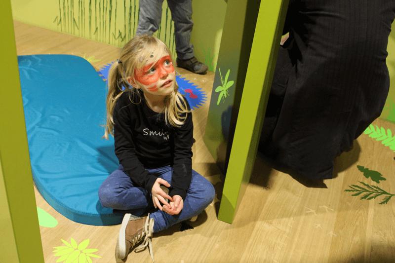Enfant maquillée assise sur le sol de Crapahut : la drôle de forêt