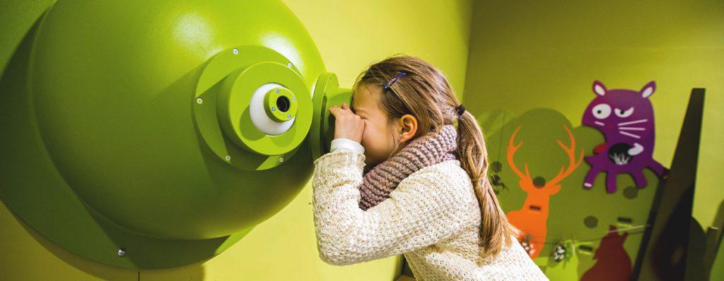 Fille qui regarde à travers des binoculaires animaux