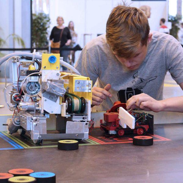 Garçon en train de peaufiner son robot lors du concours robotix's Junior