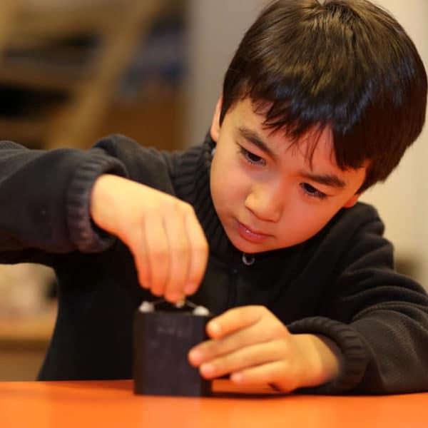 Enfant asiatique qui teste l'électricité en atelier