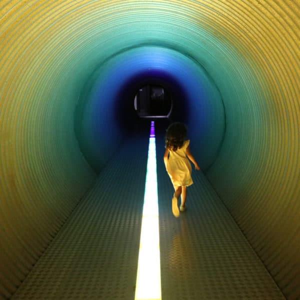 Enfant qui court dans le tunnel arc-en-ciel