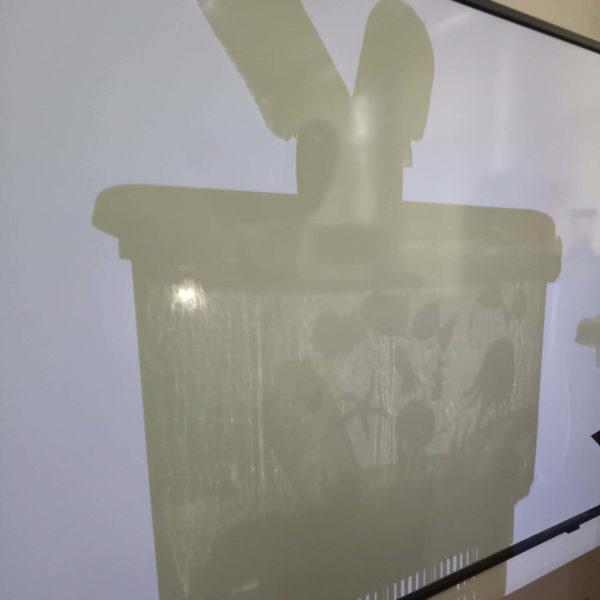 Oeuvre en shadow art : baleine qui plonge dans un océan de déchets