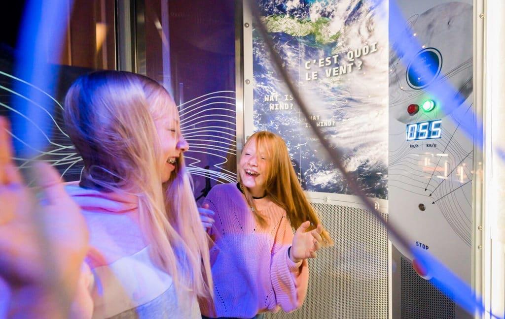 Deux filles dans un simulateur de vent, les cheveux en l'air