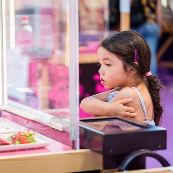 Petite fille qui observe une vitrine de l'expo Nature