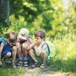 Enfants accroupis à trois dans les jardins